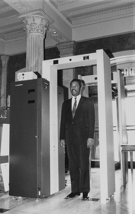 Rep. Donald M. Payne, D-N.J., going through the bomb vapor detector system. You stand under it for about 5 seconds until the green light comes on clearing you. Jan. 29, 1991. (Photo by Maureen Keating/CQ Roll Call via Getty Images)