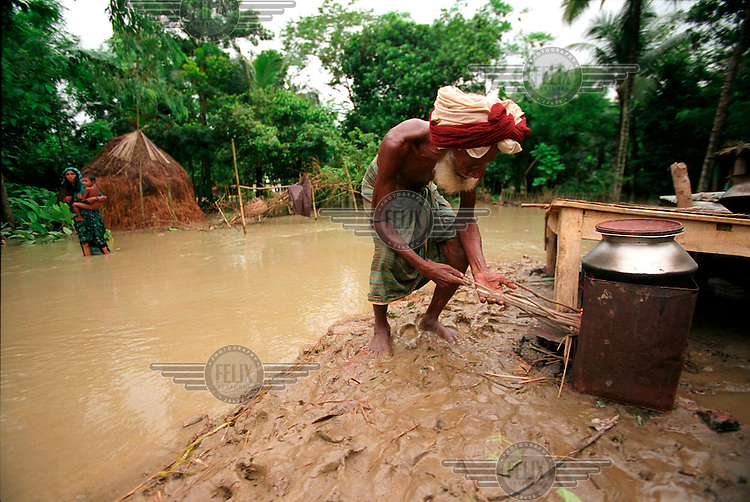 A man cooks a meal, having lost his house to flood waters. Monsoon rains caused flooding in 40 of Bangladesh's 64 districts, displacing up to 30 million people and killing several hundred.