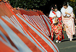 Kimono-clad 20-year-old Japanese women walk past a red and white curtain hung at times of celebration as they make their way to an event to mark Coming-of-Age Day in Tokyo, Japan on Monday Jan. 11, 2009. Japanese enter adulthood at 20, when they can legally smoke, drink alcohol and vote, though debate is heating up as to whether or not the age should be lowered to 18 in line with many advanced countries. Indeed, the Japanese government plans to lower the voting age to 18 as of mid-2010.   .Photographer: Robert GilhoolyCOMING OF AGE