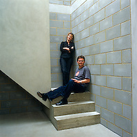 A portrait of the architect Julian Powell-Tuck and his wife Dinah Hall on the staircase of their contemporary London home