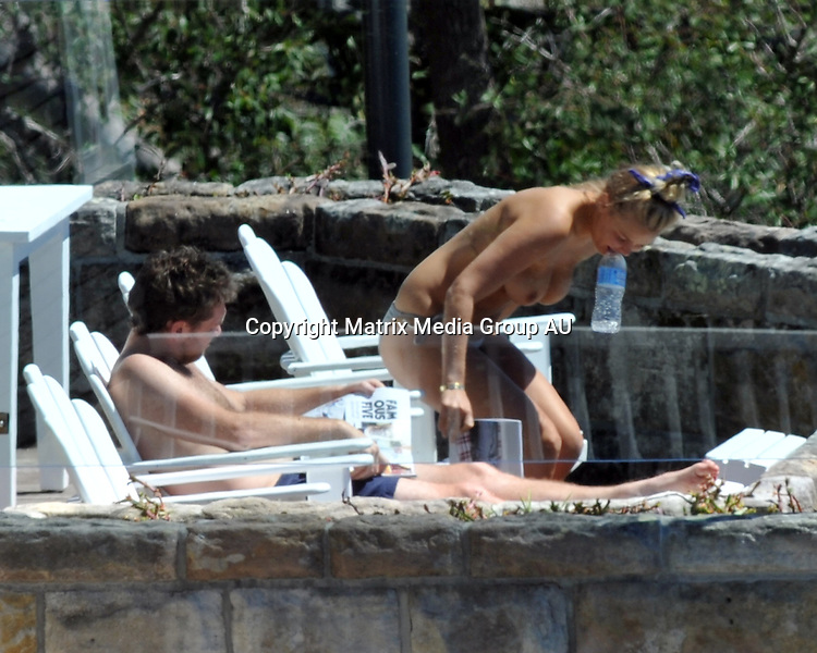 15 OCTOBER 2013 SYDNEY AUSTRALIA<br /> <br /> EXCLUSIVE PICTURES <br /> <br /> Lara Bingle pictured with Sam Worthington relaxing by the pool at their northern beaches love nest. In scenes reminiscent of Kate Middleton's topless romp with Prince Willam in France the new couple relaxed by the pool reading magazines.