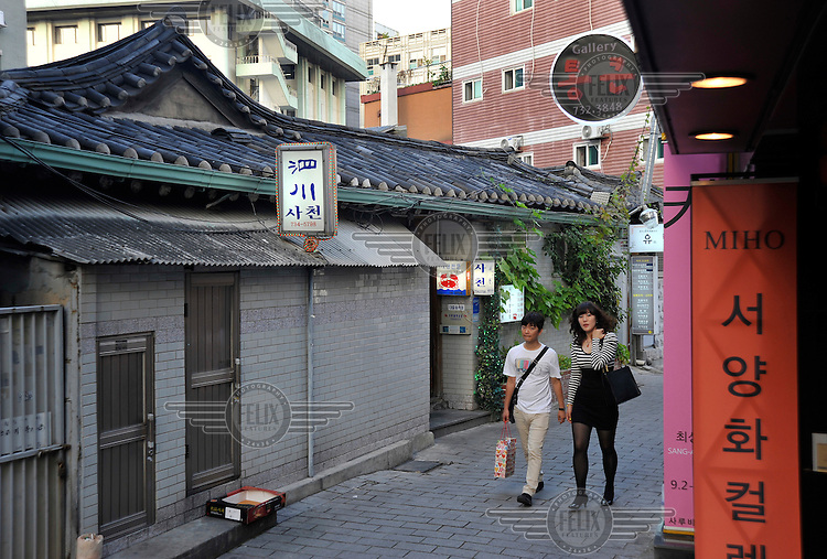 People walk down a quiet street in the Insadong district.