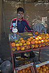 Boy squeezing fresh oranges to make juice at a roadside stall, Morocco, north Africa