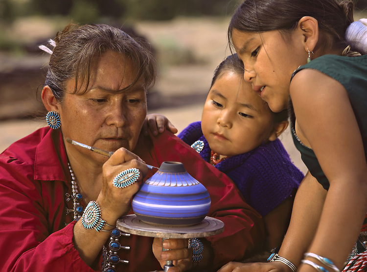 With her daughters, Joelle and Kammi Til Yazzie, studying every move, Jacqueline Hunter delicately etches elaborate Navajo designs on her vase.