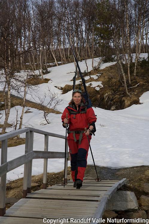 Jente krysser bro med ski på ryggsekken ---- Girl crossing bridge with skis on back pack