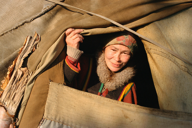 Nadia, a Nenets woman, peers out of her family's summer tent. Yamal, Western Siberia, Russia.