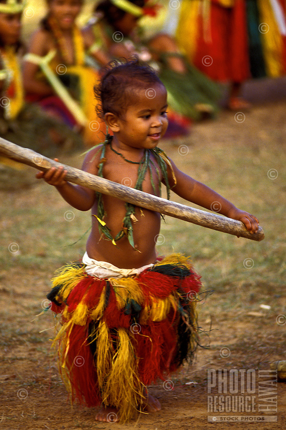 Young native girl infant wearing traditional ceremonial costume plays at performing traditional stick dance in Ma Village, Yap, Micronesia.