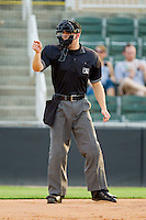 Home plate umpire Charlie Tierney makes a strike call during the South Atlantic League game between the Augusta GreenJackets and the Kannapolis Intimidators at CMC-Northeast Stadium on May 2, 2012 in Kannapolis, North Carolina.  The GreenJackets defeated the Intimidators 9-6.  (Brian Westerholt/Four Seam Images)