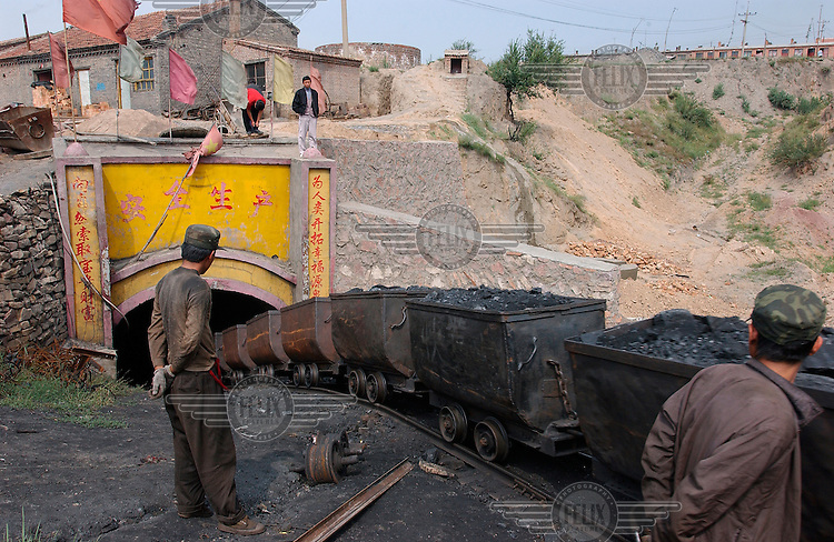Coal trucks emerge from a small coal mine. The miners live in the houses to the top right of the picture.Photo: Dermot Tatlow/Panos Pictures/Felix Features