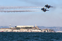 Blue Angels F-18 Hornets in diamond formation pass over Alcatraz during a 2019 San Francisco Fleet Week flight demonstration.