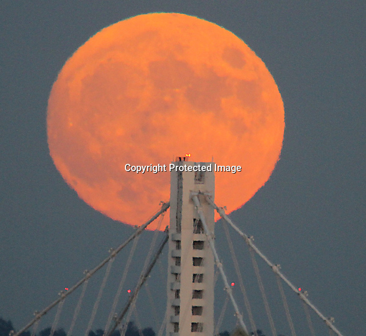 The October full moon rose over the  Oakland eastward Spand Tower as seem from the Fisherman Wharf in San Francisco.