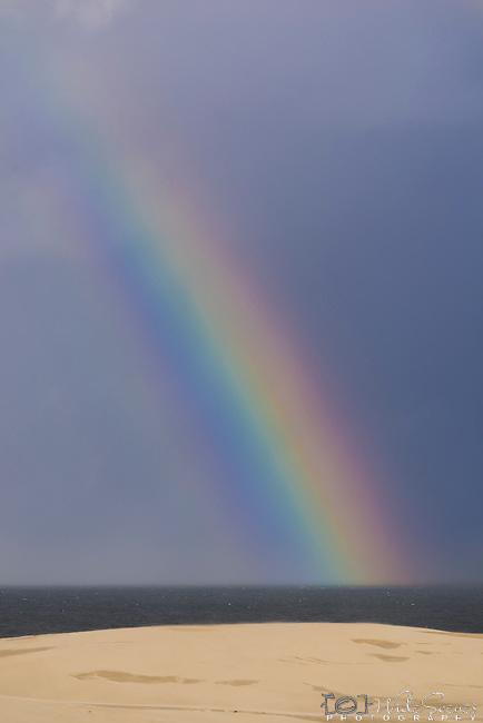 Rainbow in the sea from the sand dunes. Stockton Beach Sand dunes Worimi Conservation Lands. Anna Bay, Port Stephens, NSW, Australia