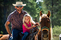 A father, daughter and horse pause from a cattle drive for a portrait. <br />
