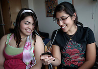 05182009- Two Seattle University students share a tune as they listen to an IPod in their Campion dorm room.