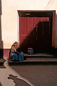 Paucartambo, Peru. A Quechua woman in traditional dress sitting in front of a closed door, half in shadow.