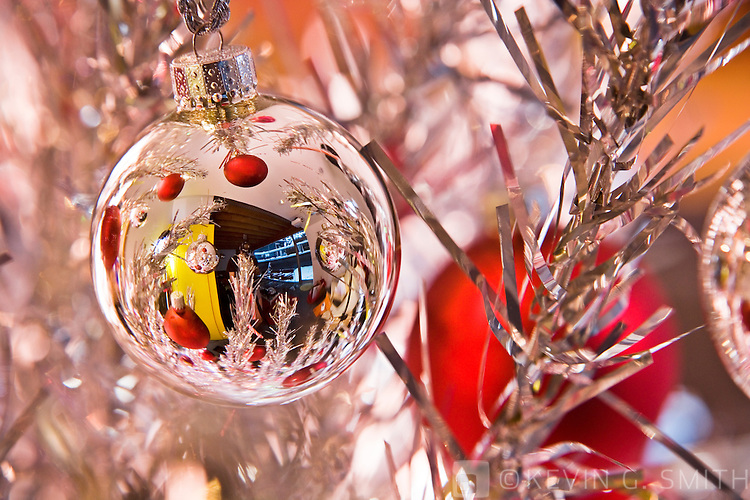 Close up of silver reflective glass ball Christmas ornament hanging on 60's retro aluminum christmas tree, selective focus.