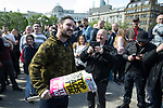 "© Joel Goodman - 07973 332324 . 11/06/2017 . Manchester , UK . A demonstrator eats a piece of an anti-fascists placard that was grabbed from anti-fascist protesters . Demonstration against Islamic hate , organised by former EDL leader Tommy Robinson's "" UK Against Hate "" and opposed by a counter demonstration of anti-fascist groups . UK Against Hate say their silent march from Piccadilly Train Station to a rally in Piccadilly Gardens in central Manchester is in response to a terrorist attack at an Ariana Grande concert in Manchester , and is on the anniversary of the gun massacre at the Pulse nightclub in Orlando . Photo credit : Joel Goodman"