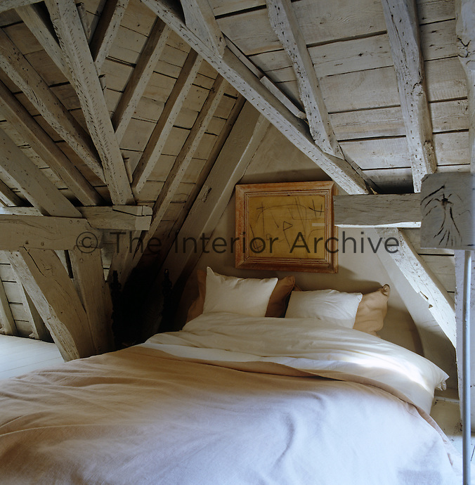 In this attic bedroom the double bed is tucked into a cosy alcove