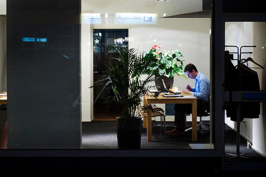 Nederland, Rotterdam, 28 nov 2011.Kantoor aan de straat. Man zit hard te werken in zijn zaak..Foto(c): Michiel Wijnbergh
