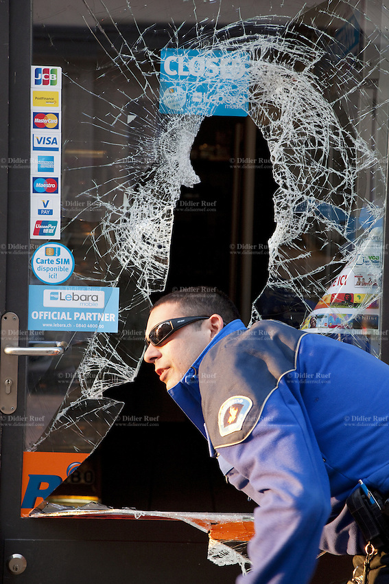 Switzerland. Geneva. Paquis neighborhood. A police officer controls the door of a shop which was burgled at night. A burglar broke into the shop by breaking the entrance glass door. The policeman is wearing under his jacket a ballistic vest, bulletproof vest or bullet-resistant vest which is an item of personal armor that helps absorb the impact from knives, firearm-fired projectiles and shrapnel from explosions, and is worn on the torso. Soft vests are made from many layers of woven or laminated fibers and can be capable of protecting the wearer from small-caliber handgun and shotgun projectiles. 28.03.12 © 2012 Didier Ruef..