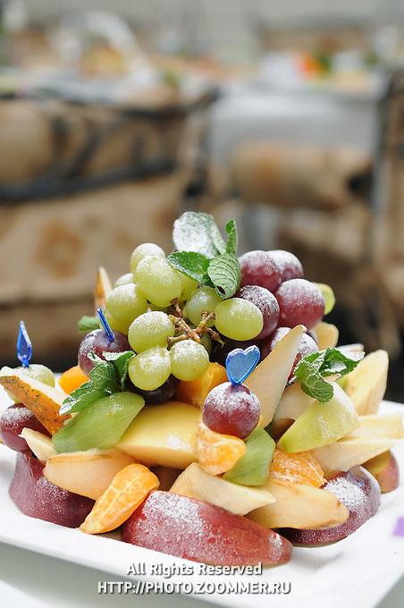 Fruit salad (grape, apple, pear, orange, mix) on a plate in fine restaurant