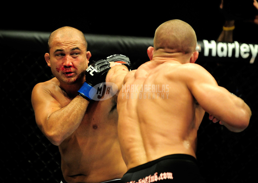 Jan. 31, 2009; Las Vegas, NV, USA; UFC fighter B.J. Penn (left) is punched by Georges St-Pierre during the welterweight championship in UFC 94 at the MGM Grand Hotel and Casino. St-Pierre defeated Penn with a fourth round TKO. Mandatory Credit: Mark J. Rebilas-