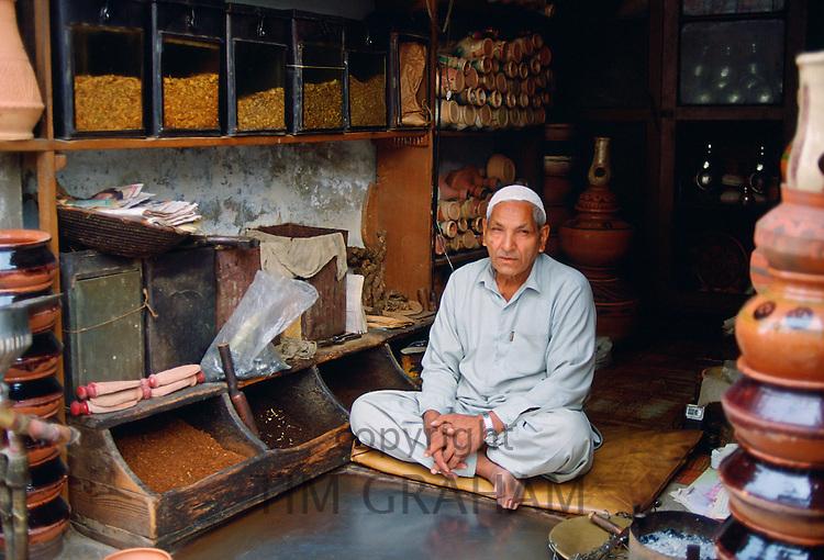 Shopkeeper  sitting cross-legged in his shop selling tobacco, Islamabad, Pakistan