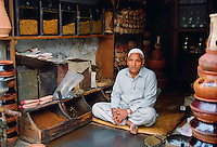 Shopkeeper  sitting cross-legged in his shop selling tobacco, Islamabad, Pakistan