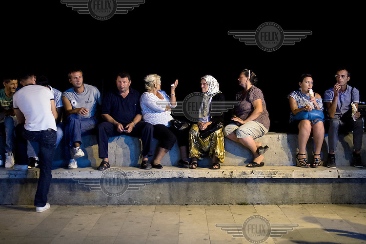 Holidaymakers sit on the sea wall in Ulqin watching the nightly passegiata. Ulqin is the traditional holiday place for Kosovo Albanian families, although recent years have seen an influx of Bosniaks (Bosnian muslims) in what may be a reflection of the lack of reconciliation in post-war Balkan societies.....
