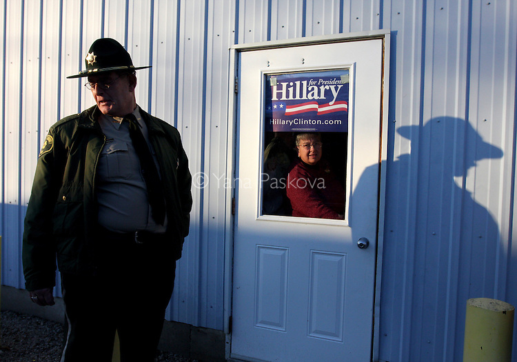 "A policeman guards the door to the Donnellson Fire Department, where U.S. Presidential Hopeful Sen. Hillary Clinton (D-NY) campaigns on December 18, 2007, in Donnellson, Iowa. Clinton is beginning her ""Every County Counts"" tour in Iowa in preparation for the January 3 caucus in the state. Photo by: Yana Paskova for The New York Times.."