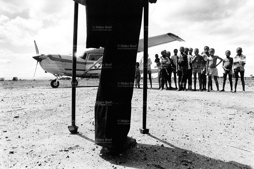 """Mozambique. Province of Tete. Zobue is a small village in the bush. A man who lost his leg on a mine and a group of children stand near the plane which soon will take off. The village can only be reached by plane. Because of the war between the Government and the rebel of the Frelimo party, the roads are either mined or too dangerous to travel on. The airplane is part of the  """"Flying Doctors"""" programm ran by the non governmental organisation (ngo) Médecins Sans Frontières (MSF) of Belgium. © 1992 Didier Ruef"""