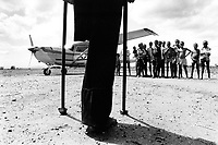 "Mozambique. Province of Tete. Zobue is a small village in the bush. A man who lost his leg on a mine and a group of children stand near the plane which soon will take off. The village can only be reached by plane. Because of the war between the Government and the rebel of the Frelimo party, the roads are either mined or too dangerous to travel on. The airplane is part of the  ""Flying Doctors"" programm ran by the non governmental organisation (ngo) Médecins Sans Frontières (MSF) of Belgium. © 1992 Didier Ruef"