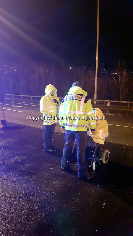 """Pictured: A paramedic and a police officer see to a man found to be riding his electric wheelchair on a dual carriageway in Llantrisant, south Wales, UK<br /> Re: A man in an electric wheelchair was stopped by police after being spotted on a dual carriageway in Rhondda Cynon Taff.<br /> The man was making his way down the """"fast lane"""" on the A4119 in Llantrisant by mistake, South Wales Police said.<br /> Officers arrived and made sure the area was safe following the incident on Saturday evening.<br /> The man was taken to Royal Glamorgan Hospital for treatment, police said."""