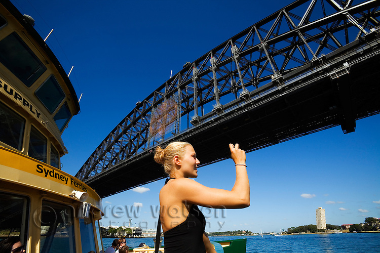 A woman photographs the Harbour Bridge from a Sydney ferry.  Sydney, New South Wales, AUSTRALIA