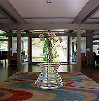 A view of the entrance hall with a large round glass table on a rug designed by Gordon Lindsay