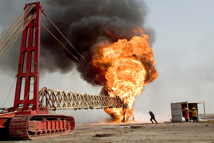 "Firefighters from the KWWK (Kuwait Wild Well Killers) attempt to extinguish an oil fire in the Rumeilah Oil Field by guiding a ""stinger"" that will pump drilling mud into the hemoraging, flaming well. Drilling mud, under high pressure, is pumped through the stinger into the well, stopping the flow of oil and gas. Many of the wells are 10,000 feet deep and produce huge volumes of oil and gas under tremendous pressure, which makes capping them difficult and dangerous. (Supporting image from the project Hungry Planet: What the World Eats.)"