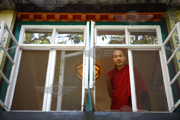 The Seventeenth Karmapa, Ogyen Drodul Trinley Dorje, stands at a window of the Norbulingka Tibetan Cultural Institute, Dharamsala. In 1992 a 7-year-old Tibetan nomad, Apo Gaga, was recognised as the Seventeenth Karmapa and went to live in Tolung Tsurphu Monastery, the historic seat of the Karmapas. He escaped Tibet for India at the turn of the millennium in order to continue without interference the primary role of the Karmapa, preserving and propagating the Buddhist teachings of Tibet.