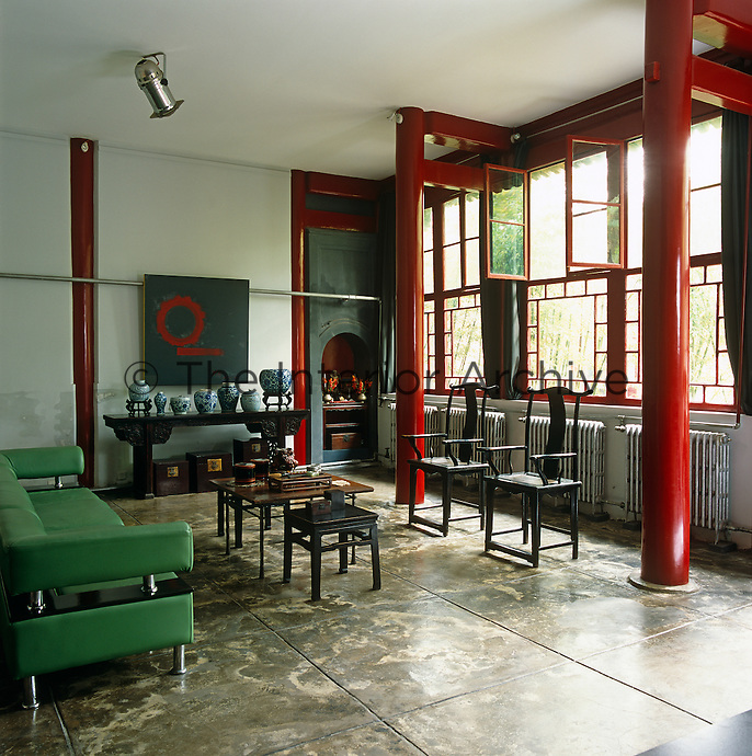 A modern green sofa bought in Beijing contrasts with a pair of 19th century Chinese chairs and a series of coffee tables in this loft-style living room