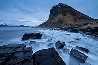 Slettind mountain peak risies over damaged stone breakwater at Myrland, Flakstadøy, Lofoten Islands, Norway