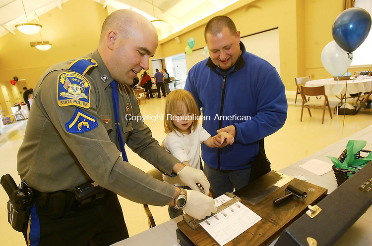 SOUTHBURY, CT 4/14/07- 041407BZ14- Connecticut State Trooper First Class John Moreno fingerprints Lilliana Spagnoletti, 3, of Oakville, as her father David Spagnoletti, helps during the 1st annual recruitment expo sponsored by the Foster Adoptive Mission (FAM) at Sacred Heart Church in Southbury Saturday.  FAM is a federally-funded colllaborative of regional organization dedicated to placing children in safe, nurturing homes in Northwest Connecticut.  The fingerprints were given to the parents to keep on file in case of emergency.<br /> Jamison C. Bazinet Republican-American
