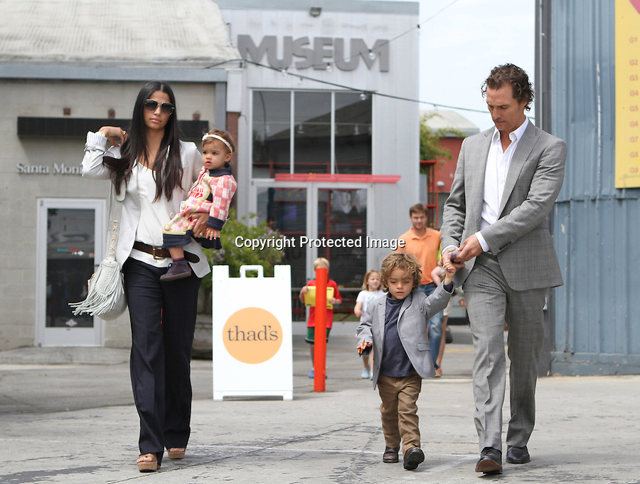 June 5th 2011....Matthew McConaughey & Camila Alves leaving church in Malibu California with their kids. Matthew was wearing a matching gray suit jacket so Levi felt pretty cool. Daughter Vida was carried by Camila wearing a very cute white red baby jump suit. Camila was also carrying a big white leather purse handbag . ..AbilityFilms@yahoo.com.805-427-3519.www.AbilityFilms.com..