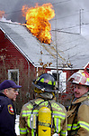 Town of Manchester firefighters standby as fire pours through the roof of this home on McKee St in East Hartford, Conn.,  Thursday,  1/22/04, the fire was fed by natural gas making it impossible for firefighters to enter the house until the gas company could shut off the flow by that time the building was structurally unstable,  fire officals said, no one was injured in the blaze. (AP Photo/Journal Inquirer, Jim Michaud)
