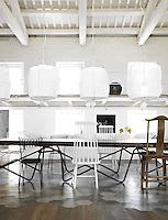 Five cylindrical suspension lamps by Mark Eden Schooley hang above the ancient table and its collection of mismatched chairs in the dining area