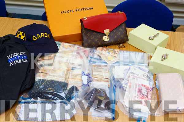 Over €100,000 of cash including sterling, Rolex watches, Louis Vuitton bags some of the haul that the Criminal Assests Bureau and Killarney Gardai seized in Killarney Tuesday morning
