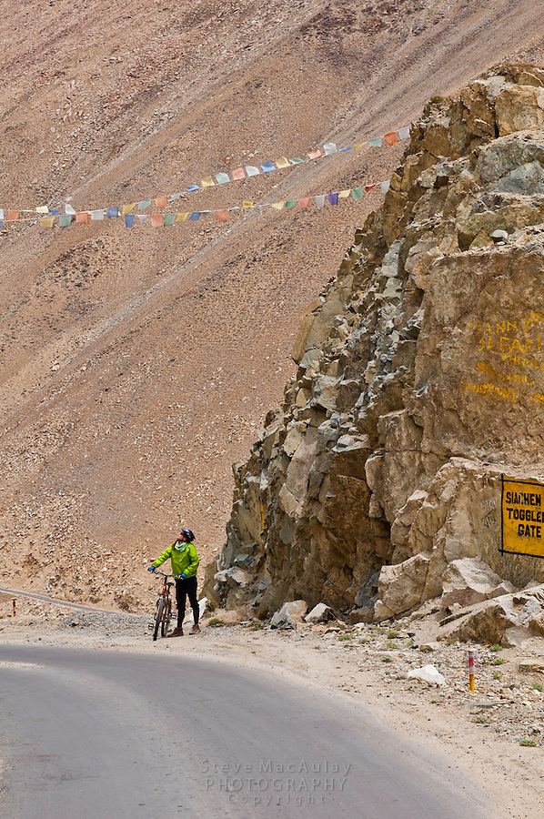 """Mountain biker at """"Siachen Toggler's Gate"""" on the highest motorable road in the world,  Himalayan Mountains, Ladakh, India."""