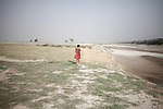 child walking on a char island around farrakka barage dam. The river is getting smaller by the years and more char islands are coming out during the dry season