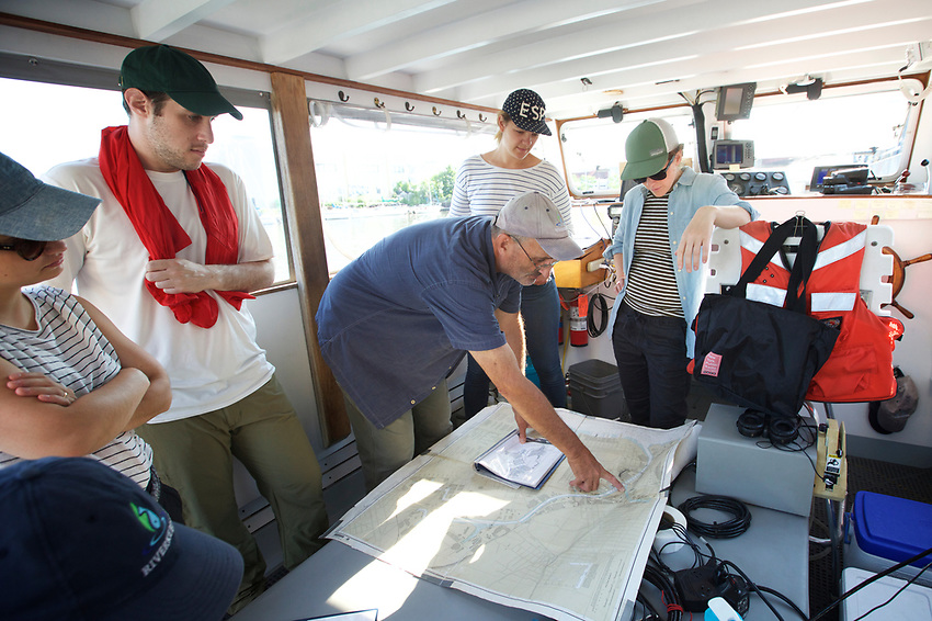 Queens, NY - July 10, 2017:  Captain John Lipscomb tells guests from Patagonia about the work his team does at the beginning of a survey of Newtown Creek with Riverkeepers, checking for pollution in the waterway.<br /> <br /> Credit: Clay Williams for Edible Queens.