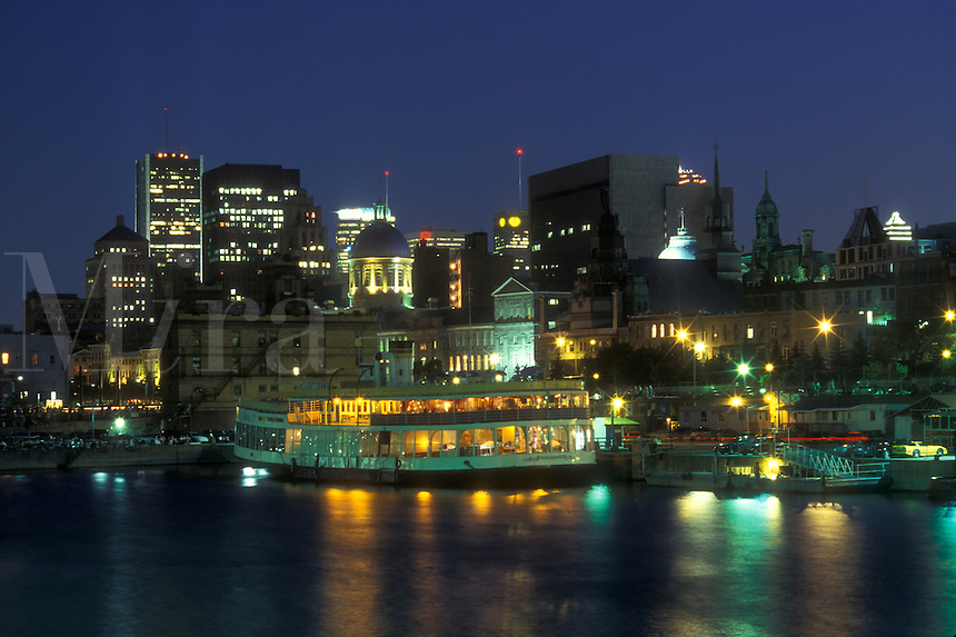 AJ0807, Canada, Quebec, Montreal, The illuminated skyline of downtown Montreal reflects in the waters of the St. Lawrence River (Fleuve Saint-Laurent) at Vieux Port in the evening.