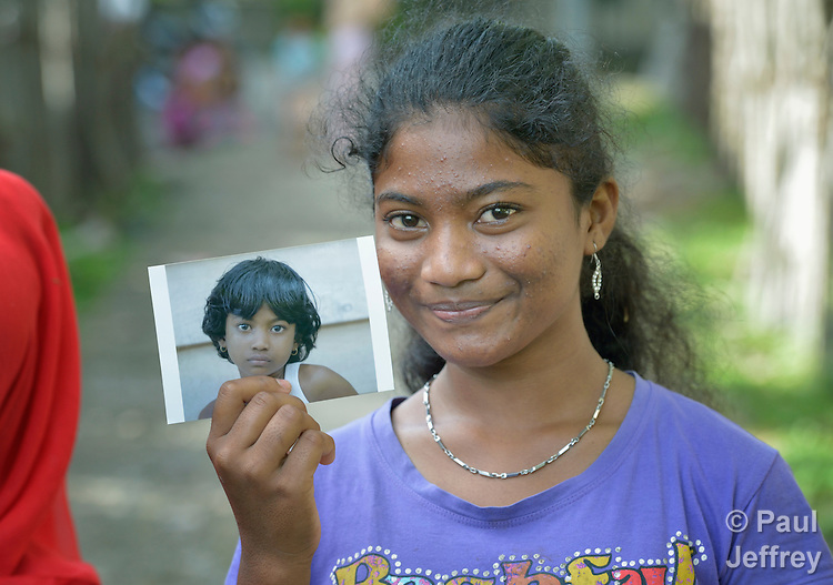 In 2014, Santi Lena, 16, holds a photo taken of her seven years earlier, in 2007, in Lhok Me, in Indonesia's Aceh province. The girl and her family were left homeless by the 2004 tsunami, but YEU, a member of the ACT Alliance, worked with the village to build new houses in a safer area, as well as help revitalize their income generating activities. The tsunami killed 221,000 people in Aceh province and left more than 500,000 displaced.