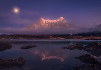 The setting moon illuminates Paine Grande on a foggy morning in Patagonia.